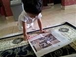 A young girl with her hands and knees on the floor reads a newspaper.