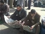 Two men sitting down outside reading newspapers.