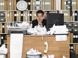 businesswoman looking overwhelmed sitting at a very very messy desk