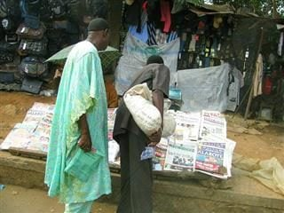Two people look over a stack of newspapers.