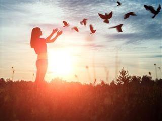 Une jeune fille qui se profile libérant une volée d'oiseaux