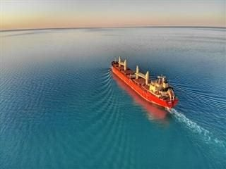 bright red commercial ship cutting through blue waters