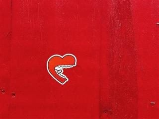 graffiti heart with a human mouth against a red background