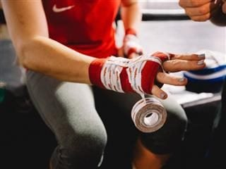 taping up a female boxer's hands before a fight