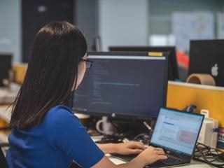 woman looking at back-end code on two computers