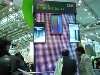 "People standing in front of a sign that says ""IBM Green Responsibility"""