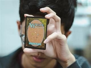 man holding magic card up against forehead