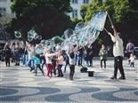 people playing in a public plaza with large bubbles