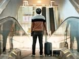 A businessman carrying luggage and a digital tablet  on an escalator - customer journey concept