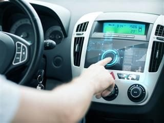 Man using in-car display to connect to the internet - connected cars