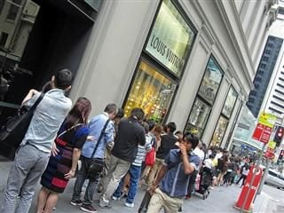People waiting outside in a line outside of a Louis Vitton store.