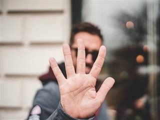man giving a high five, partially obscuring his face