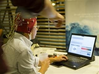 A person typing on a laptop while wearing what appears to be a cap for virtual and augmented reality sensors around his head. Another person's arm is pointing at the laptop on the top part of the photo.