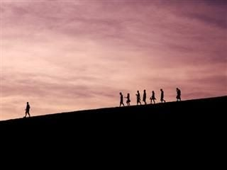 silhoutes of people walking down a hill, one person far ahead of the others