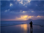 man fishing under a cloudy sky
