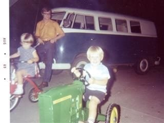Two children riding bikes while father watched from the background in 1969.
