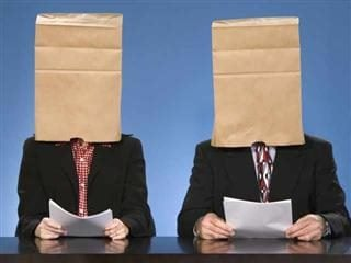 Two suited interview candidates holding resumes with bags on their heads - unconscious bias