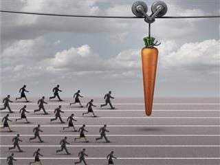 a group of businessmen and businesswomen running on a track towards a dangling carrot on a moving cable as a financial reward metaphor to motivate for a goal.