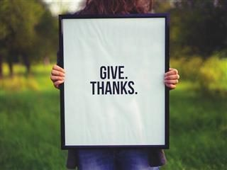 woman holding sign saying 'give thanks'