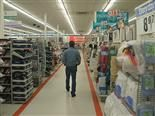 A man walks down an aisle in a department store.