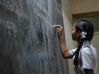 girl writing on a blackboard