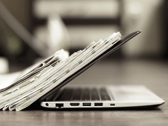 Open laptop with a stack of newspapers leaned up against it - Newsbyte concept