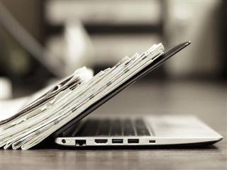 Ordinateur portable ouvert avec une pile de journaux - concept Newsbyte