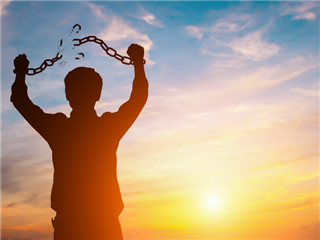 A silhouetted  man in front of a sunset. His hands are over his head as he breaks the chains
