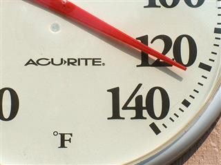 white circular outdoor thermometer showing summer heat temperature of 120 degrees fahrenheit