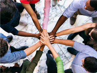 Team Of Diverse Workers Put Hands Together