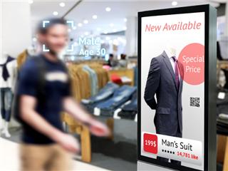 A man walking through a shopping mall, passes by a digital sign that is delivering an ads via an Out-of-Home (OOH) advertising network. There is also a a QR code in the ad.