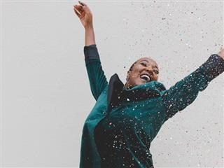 happy woman with arms in the air being sprinkled with confetti