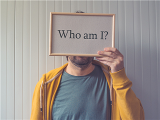 A customer holding a sign over his face that says who am I - customer behavior concept