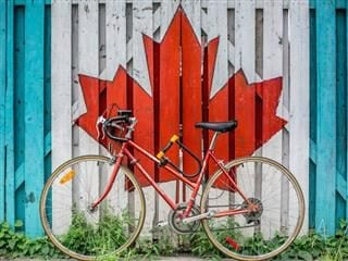 Canadian maple leaf with bicycle in front of it