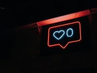 "neon sign of the ""like"" button from social media showing zero likes"