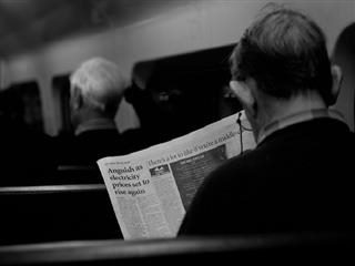 Man reading a newspaper on a train.