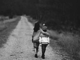two children walking arm in arm down a road