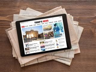 A tablet with a news app open sitting on a table atop a pile of newspapers
