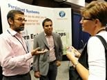 two men talking to a woman in front of a persistent systems booth at a technology conference