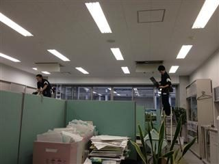 Two men work in an office with cubicles making improvements.