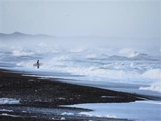 surfer walking into waves