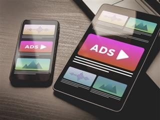 Online native video ad banner on a mobile phone sitting on a desk