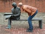 man talking to a scuplture