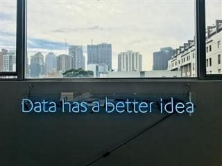 "a neon sign that says ""Data has a better idea"" with window view of city overhead"
