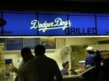 "People in front of a vendor at Dodger Stadium that is titled ""Dodger Dogs."""