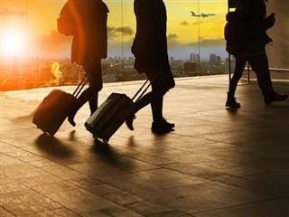 people and traveling luggage walking in airport terminal building with sun set sky at urban scene and air plane flying background