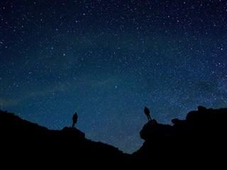 two people standing on separate rocks against a night sky