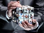 A man holding an abstract rubiks-style cube with business images - future transformation concept