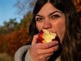 woman taking a big bite out of an apple, down to the core