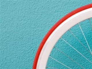 close up of a bicycle wheel against a turquoise wall